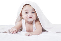 Attractive male toddler on bed. Portrait of an adorable baby boy lying on the bed while smiling on the camera under a towel Royalty Free Stock Images