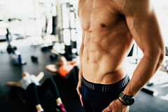 Attractive male torso in gym. Flexing abs Royalty Free Stock Photography