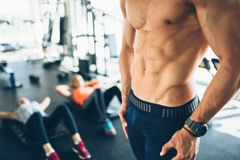 Attractive male torso in gym. Flexing abs Stock Photos