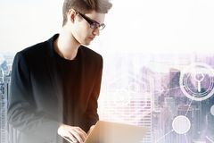 Attractive male using laptop. Attractive young european male using laptop on abstract city background. Technology and communication concept. Double exposure Stock Photography