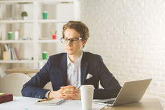 Attractive male using laptop. Portrait of attractive young male using laptop at workplace Royalty Free Stock Images