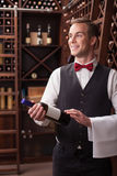 Attractive male winehouse worker is serving a Royalty Free Stock Photography