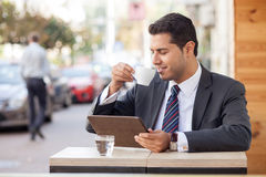 Attractive male worker is enjoying espresso in. Handsome young businessman is drinking coffee in cafeteria outdoors. His eyes are closed with pleasure. He is Royalty Free Stock Image