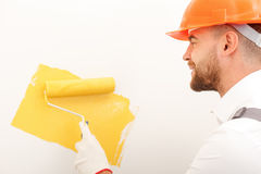 Attractive male worker is making building better. Cheerful young builder is painting wall with yellow color. He is standing and smiling. The man is holding a Royalty Free Stock Image