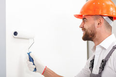 Attractive male worker is making house beautiful. Handsome young builder is painting walls with a roller. He is standing and smiling Stock Photo