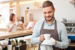 Attractive male worker is serving customers in. Cheerful young barista is working in coffee house. He is standing and drying a white cup with towel. He is Royalty Free Stock Image