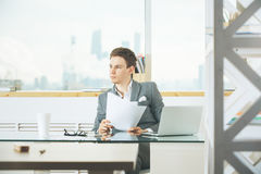 Attractive male worker working on project. Attractive european male worker doing paperwork and using laptop placed on office desktop with various items. Project Royalty Free Stock Image