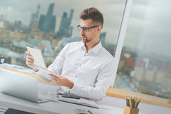 Attractive male working on project. Attractive young male working on project at modern office desk Stock Image