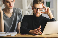 Attractive males discussing project. Portrait of attractive european males at workplace using laptop and discussing project. Teamwork concept Royalty Free Stock Photo