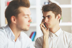 Attractive males talking on phone Royalty Free Stock Photography