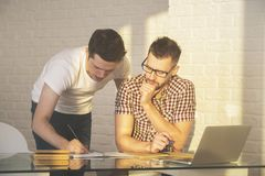 Attractive males working on project. Two attractive males working on project in modern office. Success, teamwork, discussion and meeting concept Stock Images