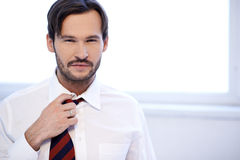 Attractive man adjusting the knot of his tie Royalty Free Stock Images