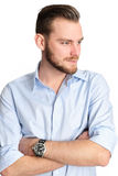 Attractive man against white background. Attractive man standing with a white white background wearing a blue shirt, feeling great Royalty Free Stock Photo