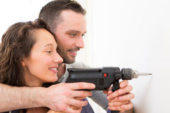 Attractive Man assisting his girlfriend using a drill Royalty Free Stock Photo