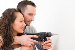 Attractive Man assisting his girlfriend using a drill Royalty Free Stock Photography