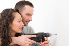 Attractive Man assisting his girlfriend using a drill Stock Photos