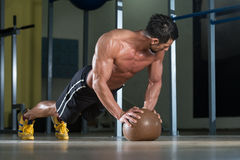 Attractive Man Athlete Performing Push-Ups On Medicine Ball Royalty Free Stock Image