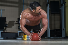 Attractive Man Athlete Performing Push-Ups On Medicine Ball Stock Photography