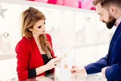 Attractive man with a beard choosing a valentine`s day gift in jewelry store. Beauty female seller presents a necklace. Jewelry store. Woman jeweler. Attractive stock images