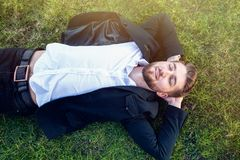 Attractive man with a beard is lying in the park royalty free stock photography