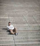 Attractive man with beard is sitting on steps.  Royalty Free Stock Photo