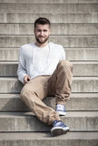 Attractive man with beard is sitting on steps Royalty Free Stock Image