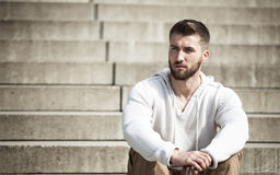 Attractive man with beard is sitting on steps.  Stock Image