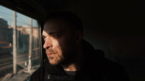 Attractive man with beard traveling by train. Handsome young male looking at window and thinking, sitting in the shadow. Pensive guy feels loneliness, goes stock footage