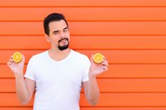 Attractive man with beard in white shirt holding in both hands halves of a cut citrus fruit standing against bright orange wall stock photography