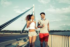 Attractive man and beautiful woman jogging together. Attractive men and beautiful women jogging together on bridge Stock Photography