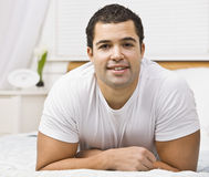 Attractive man on bed. Brunette male on bed laying on stomach.square Stock Photography