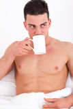 Attractive man in bed drinking coffee Stock Photo