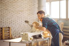 Attractive man begin doing woodwork in carpentry. Carpenter begining working on woodworking machines in carpentry shop Royalty Free Stock Photography