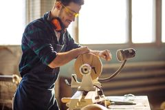 Attractive man begin doing woodwork in carpentry. Carpenter begining working on woodworking machines in carpentry shop stock photography