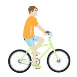 Attractive man on a bicycle. Attractive man in an orange shirt and blue shorts on a green bike on a white background Stock Photography