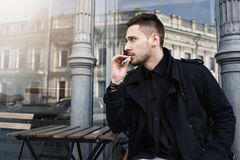 Attractive man in black clothes took sit to have cigarete. Man took sit to have cigarete, looking away thoughtfully. Magnificent city view on background Royalty Free Stock Image