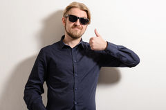 Attractive man in black sunglasses standing near a white wall holding up thumbs up.  Royalty Free Stock Photography