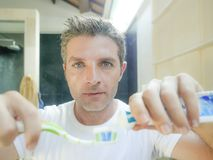 Attractive man with blue eyes at home bathroom putting paste on toothbrush for brushing tooth looking at himself on toilet mirror royalty free stock image