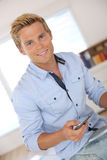Attractive man with blue shirt holding smartphone Stock Images