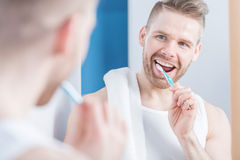 Attractive man brushing his teeth Stock Photos