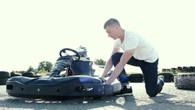 Attractive man checking tire pressure on his gocart. Before starting his race stock video footage