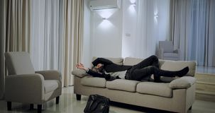 Attractive man coming from work at home very happy and charismatic jumping over the sofa in a large spacious living room stock video footage
