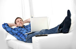 Attractive man with computer sitting on couch Stock Photography
