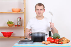 Attractive man cooking in the kitchen Stock Photography