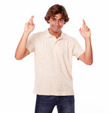 Attractive man crossing fingers while smiling Royalty Free Stock Photography
