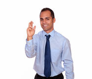 Attractive man crossing his fingers looking at you Royalty Free Stock Images