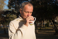 Attractive man deep in thought, drinking coffee, standing  in th Royalty Free Stock Photography