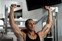 Attractive Man Doing Shoulder Press With Machine. Fit man doing shoulder presses on a weight machine at the health club Stock Photo