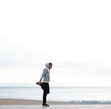 Attractive man doing stretching  on the coast Royalty Free Stock Photography