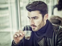 Attractive Man Drinking Coffee at Bar Table. Attractive Man Drinking Coffee while Sitting in a Bar Table with Serious Expression Stock Photo